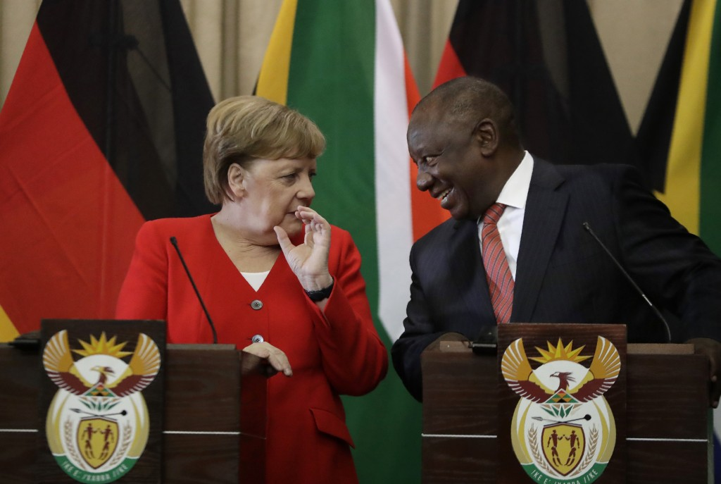 German Chancellor Angela Merkel, left, and South African President Cyril Ramaphosa react, during a press conference at the government's Union Building...