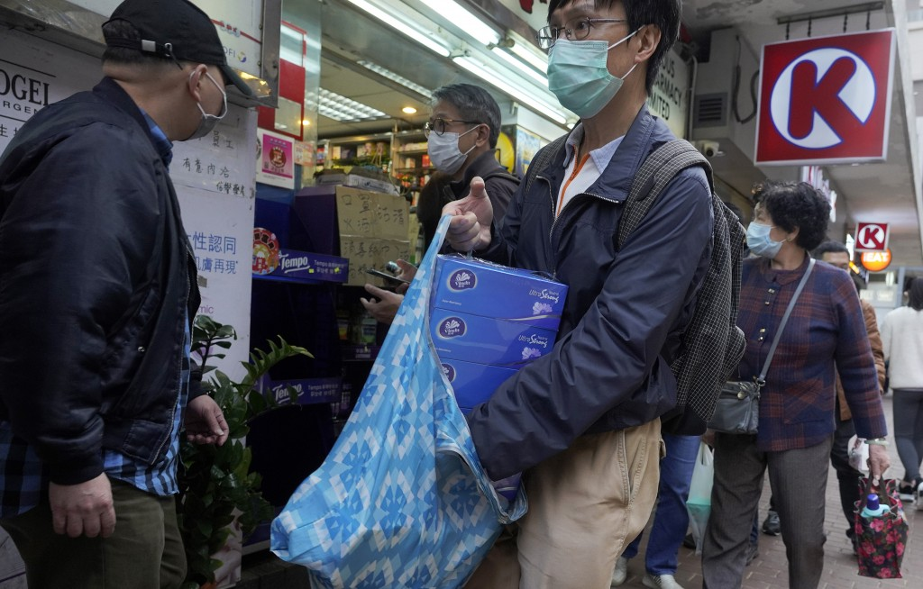 A man wearing face mask holds tissue papers after purchasing outside a pharmacy in Hong Kong, Thursday, Feb. 6, 2020. Ten more people were sickened wi...