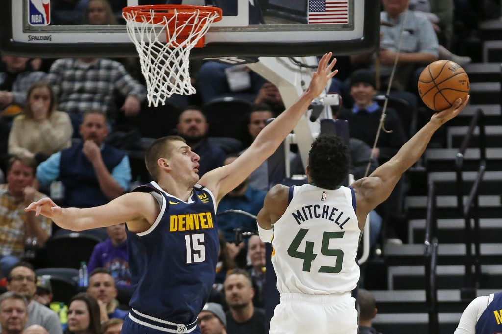 Utah Jazz guard Donovan Mitchell (45) lays the ball up as Denver Nuggets center Nikola Jokic (15) defends in the first half during an NBA basketball g...
