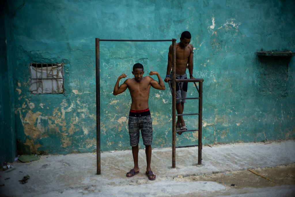 A young man strikes a pose showing off his muscles, framed by a pull up bar in Havana, Cuba, Wednesday, Feb. 5, 2020. (AP Photo/Ramon Espinosa)