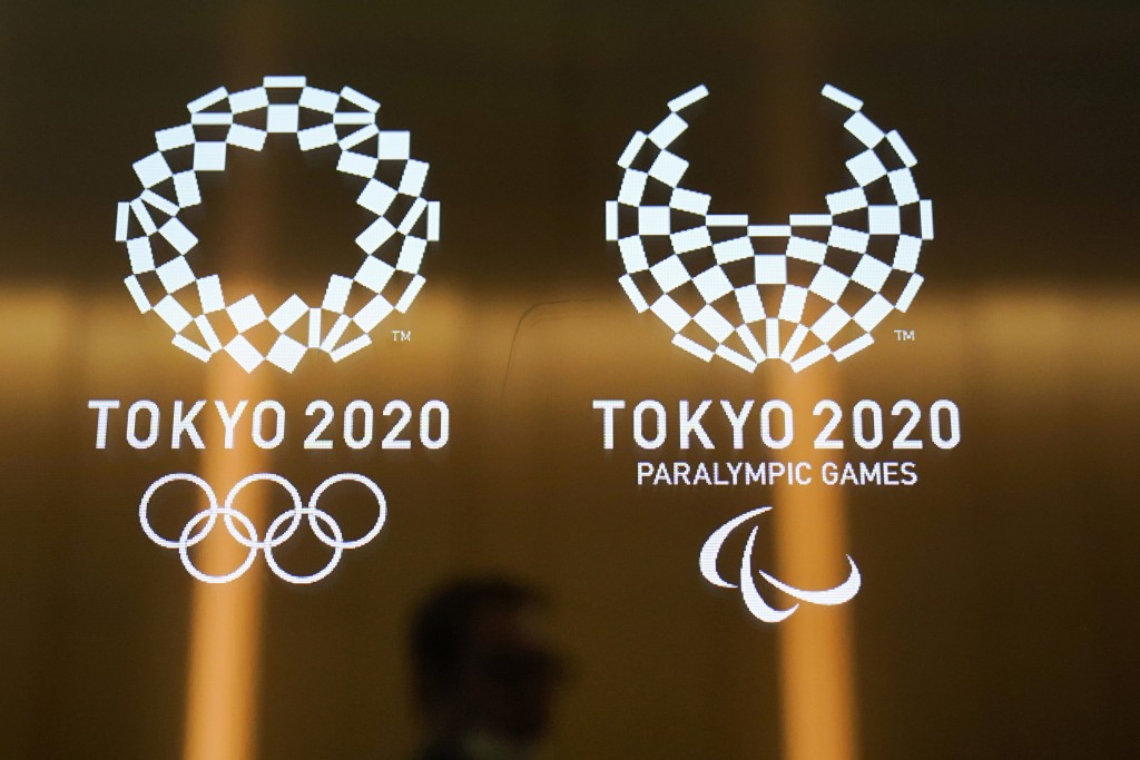 FILE - In this June 11, 2019, file photo, a man walks past the logos of the Tokyo 2020 Paralympics and Olympics in Tokyo. Tokyo Olympic and Paralympic...