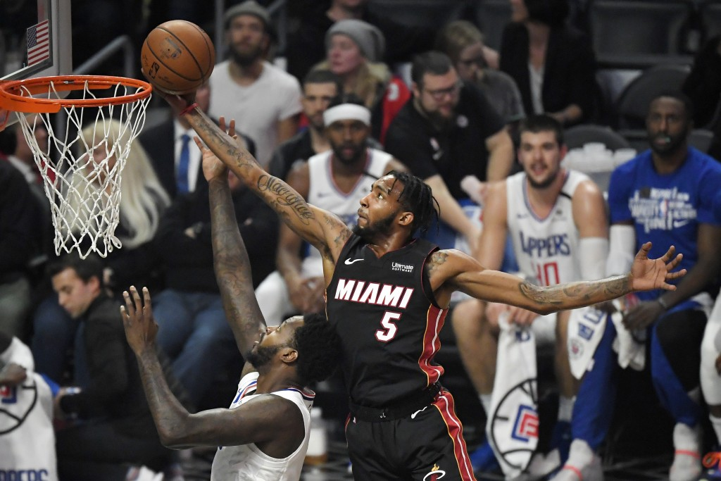 Miami Heat forward Derrick Jones Jr., right, grabs a rebound away from Los Angeles Clippers forward JaMychal Green during the first half of an NBA bas...