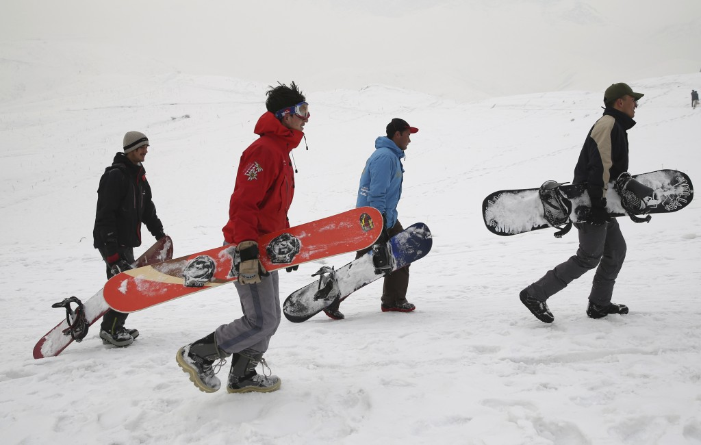 In this Friday, Jan. 24, 2020 photo, Karim Faizi 24, right, a trainer from the Afghanistan Snowboarding Federation leads a group during a practice ses...