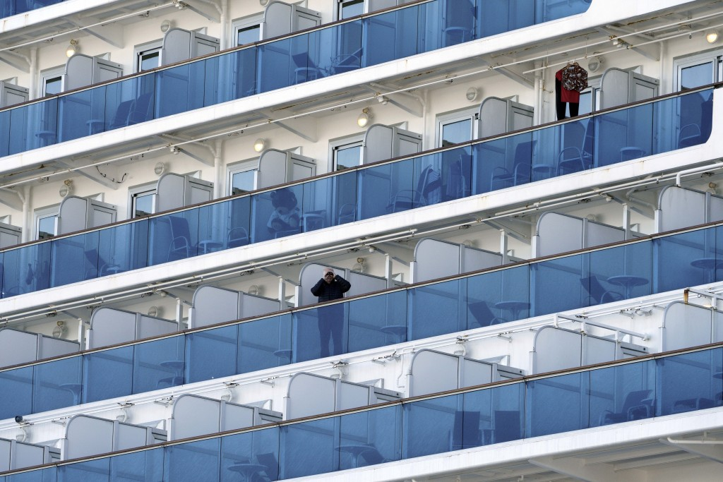 A passenger using binoculars watches from the Diamond Princess as the cruise ship is anchored at Yokohama Port for supplies replenished in Yokohama, s...