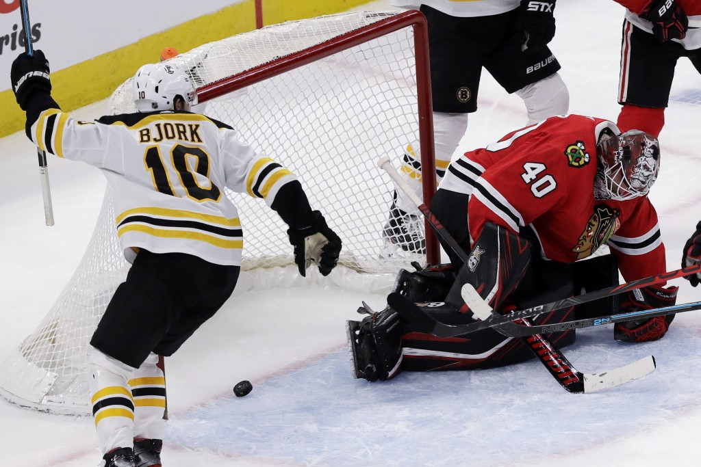Boston Bruins left wing Anders Bjork, left, celebrates after center Sean Kuraly scored on Chicago Blackhawks goalie Robin Lehner during the second per...