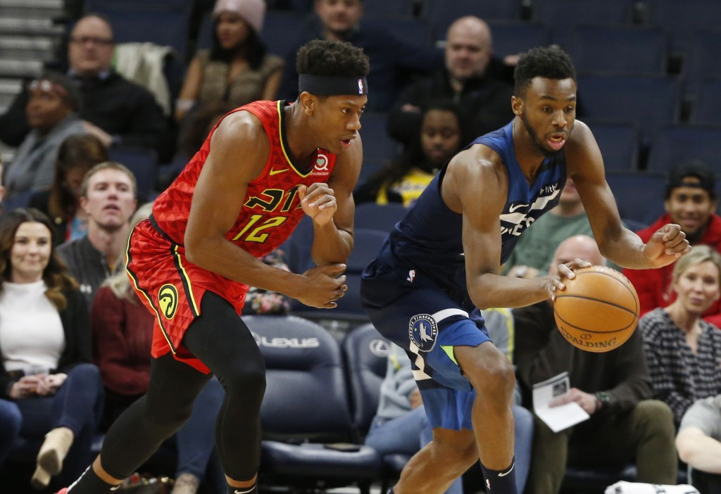 Minnesota Timberwolves' Andrew Wiggins, right, and Atlanta Hawks' De'Andre Hunter chase the ball in the first half of an NBA basketball game Wednesday...