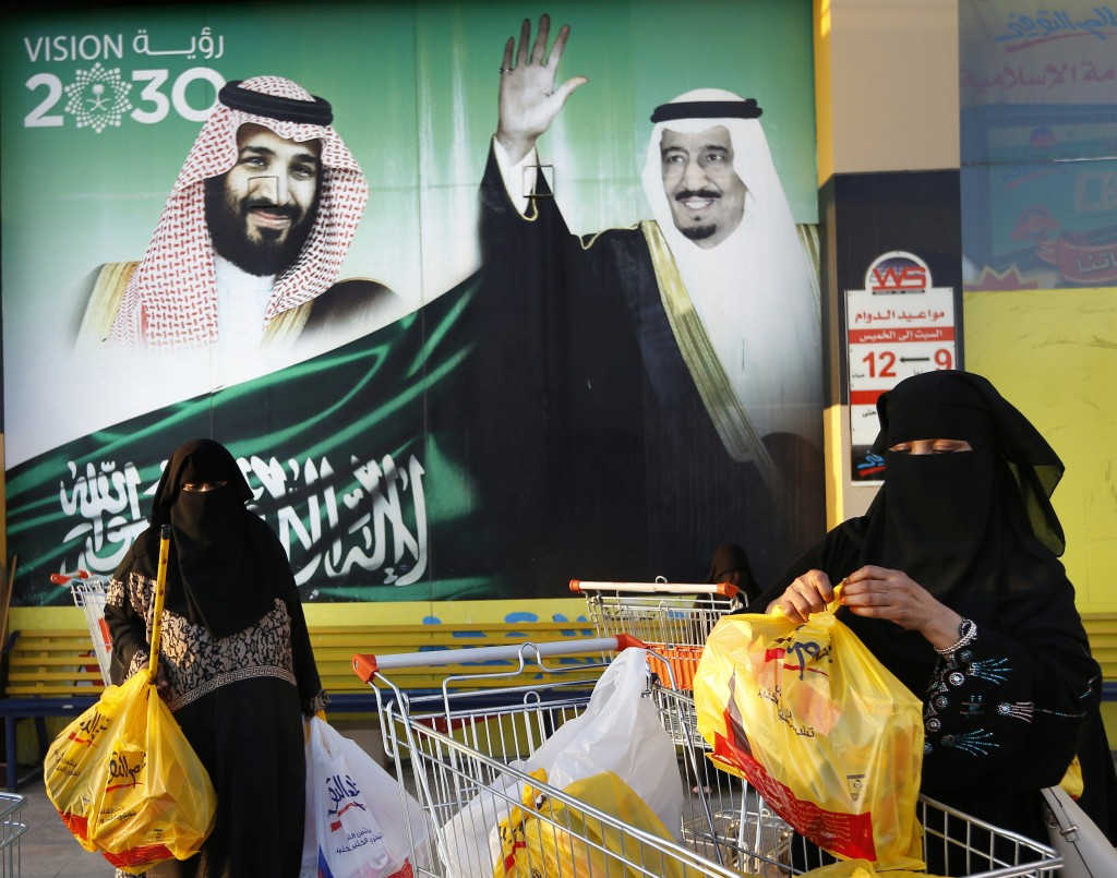In this Wednesday, Feb. 5, 2020, photo, women carry their shopping bags past a banner showing Saudi King Salman and his Crown Prince Mohammed bin Salm...
