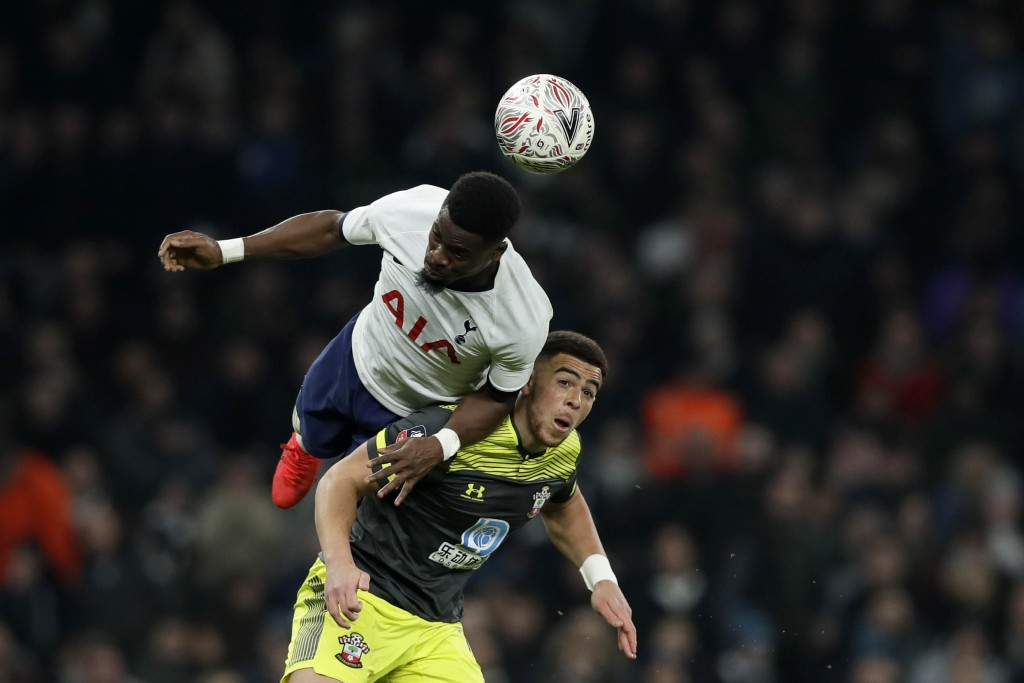 Tottenham's Tanguy Ndombele heads the ball above Southampton's Jan Bednarek, right, during the English FA Cup fourth round replay soccer match between...