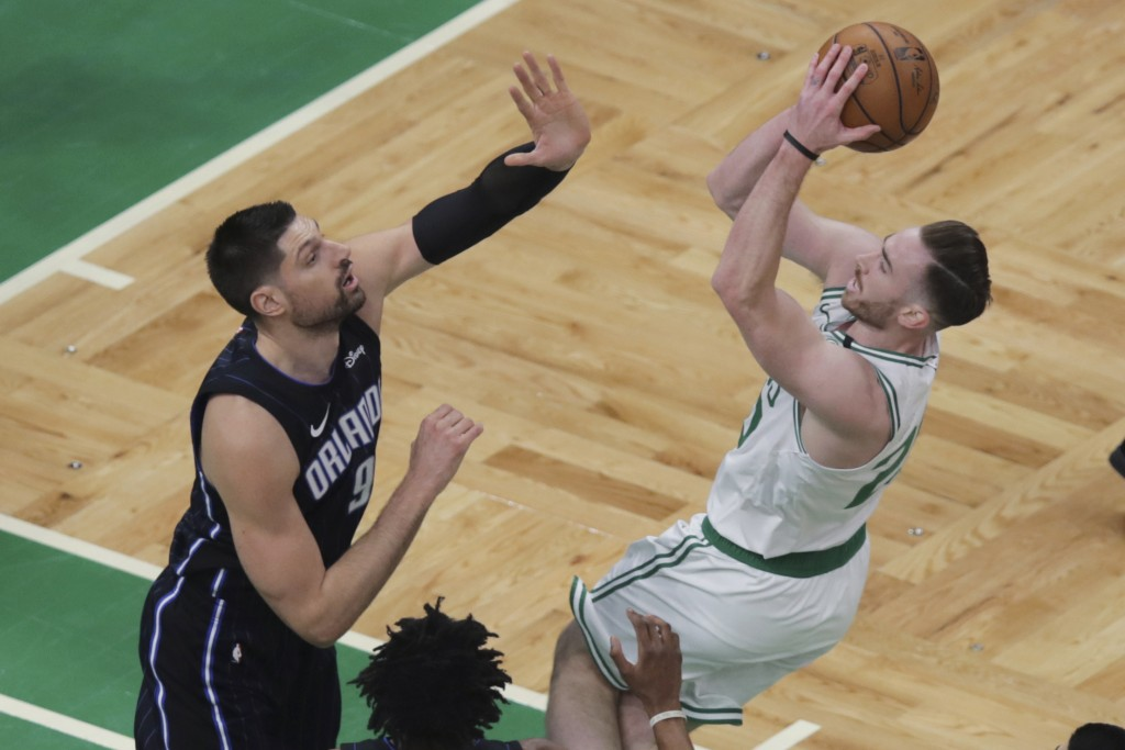 Orlando Magic center Nikola Vucevic, left, tries to stop Boston Celtics forward Gordon Hayward on a drive to the basket during the first quarter of an...