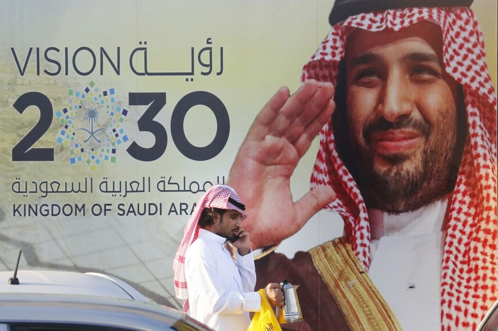 In this Wednesday, Feb. 5, 2020, photo, a Saudi man carries his coffee pot as he walks past a banner showing Saudi Crown Prince Mohammed bin Salman, o...