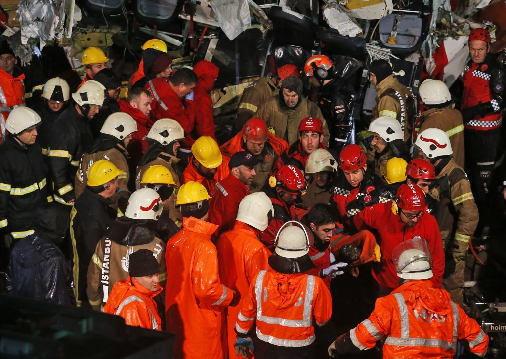 Rescue members evacuate an injured person from the wreckage of a plane after it skidded off the runway at Istanbul's Sabiha Gokcen Airport, in Istanbu...