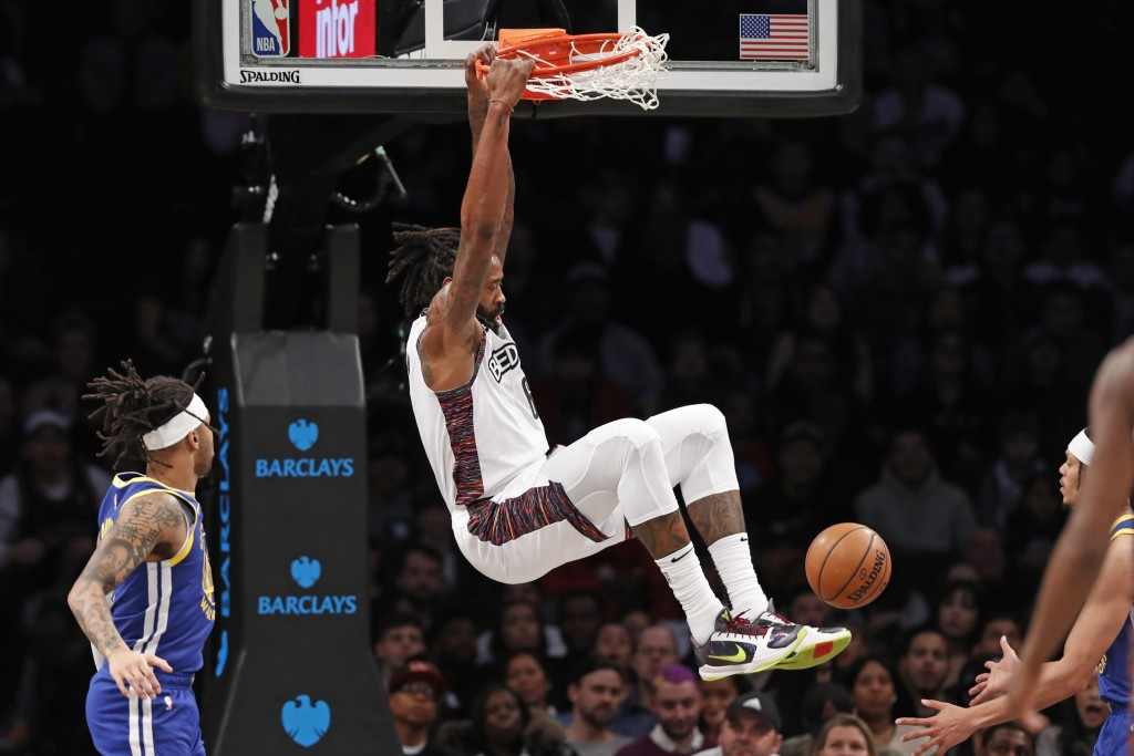Brooklyn Nets center DeAndre Jordan (6) hangs from the rim after dunking in front of Golden State Warriors guard D'Angelo Russell, left, during the fi...