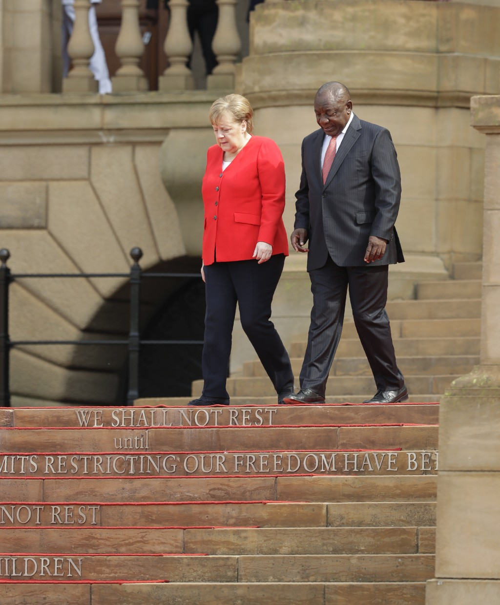 German Chancellor Angela Merkel, left, and South African President Cyril Ramaphosa, arrive at a welcoming ceremony at the government's Union Buildings...