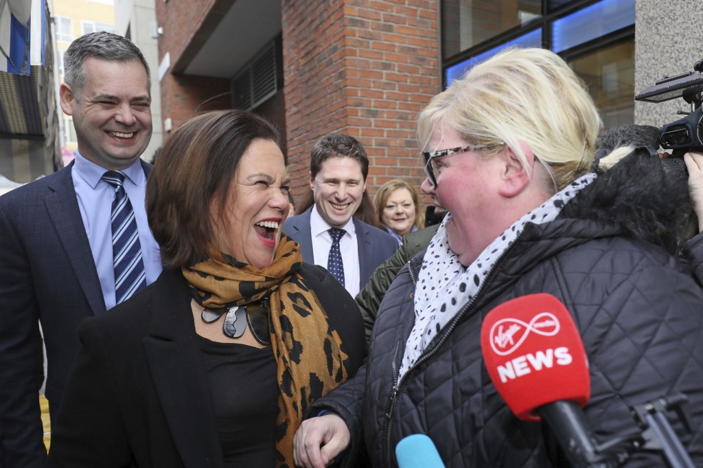 Sinn Fein leader Mary Lou McDonald, center, and Pearse Doherty, left, speak to members of the public during a campaign walkabout in central Dublin, Th...