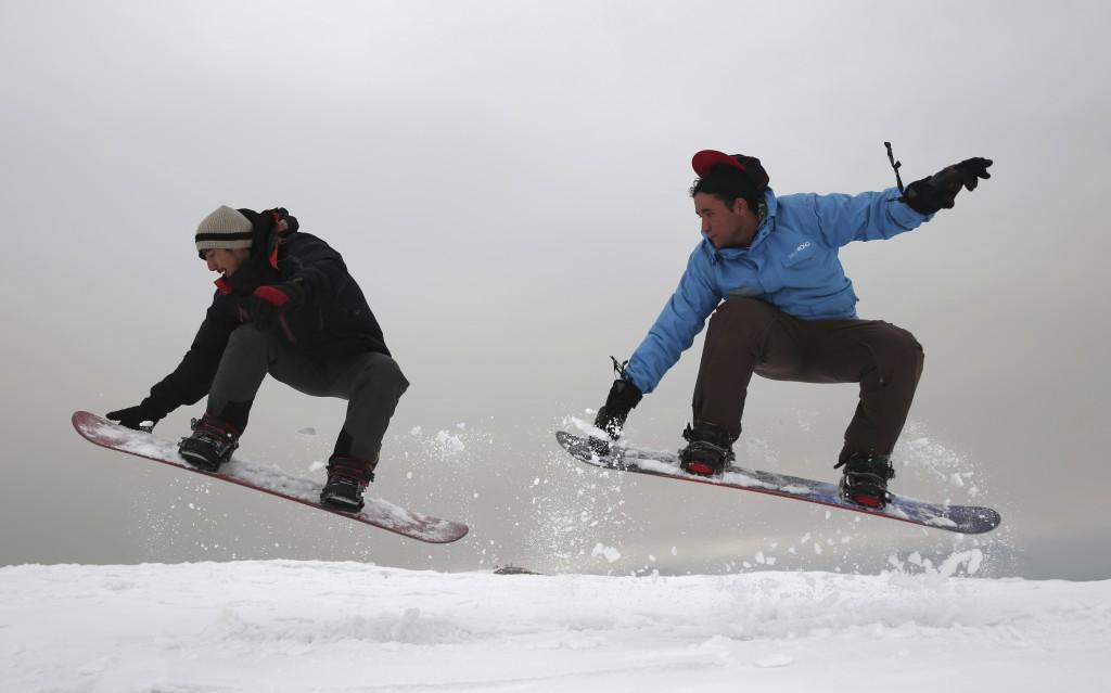In this Friday, Jan. 24, 2020 photo, Ahmad Sorush, 22, left, and Nizaruddin Alizada, 20, make a jump on the snow-covered hillside known as Kohe Koregh...