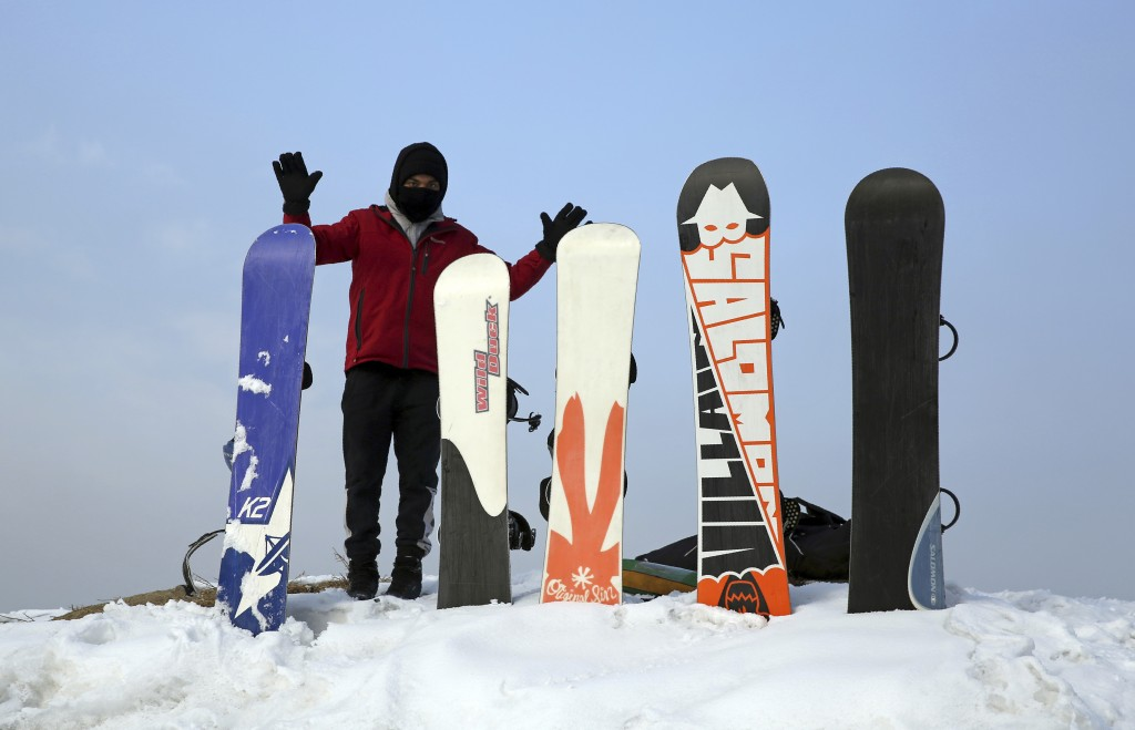 In this Friday, Jan. 24, 2020 photo, Ahmad Romal Hayat, 22, who founded the Afghanistan Snowboarding Federation, adjust snowboards during a practice s...
