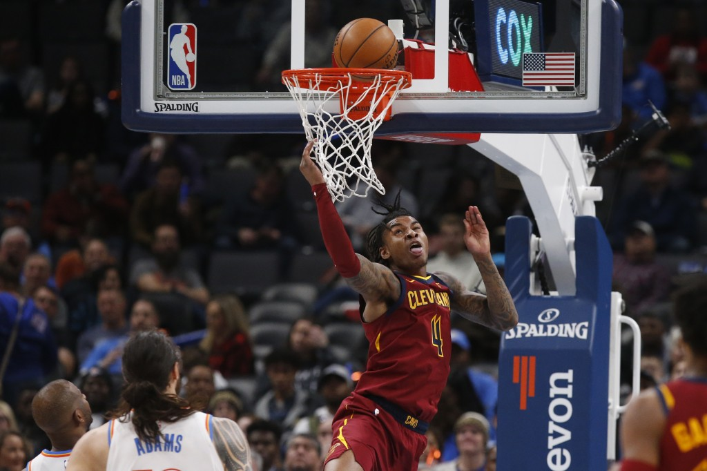 Cleveland Cavaliers guard Kevin Porter Jr. (4) watches his shot in front of Oklahoma City Thunder guard Chris Paul, left, and center Steven Adams, sec...
