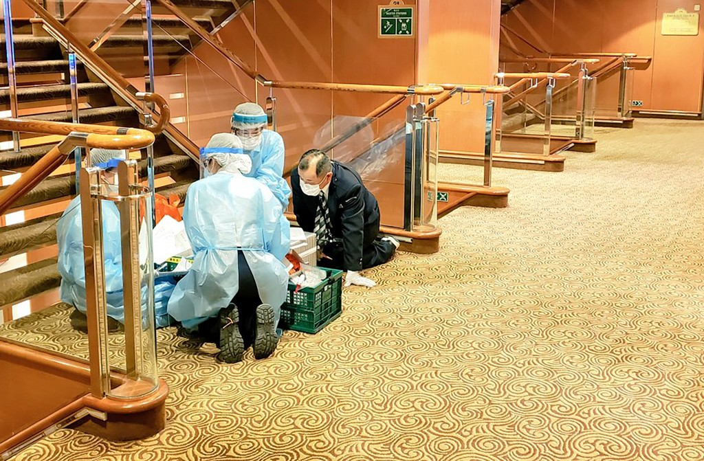 In this Tuesday, Feb. 4, 2020, photo taken by the passenger, medical workers in protective suits talk togther on the cruise ship Diamond Princess anch...