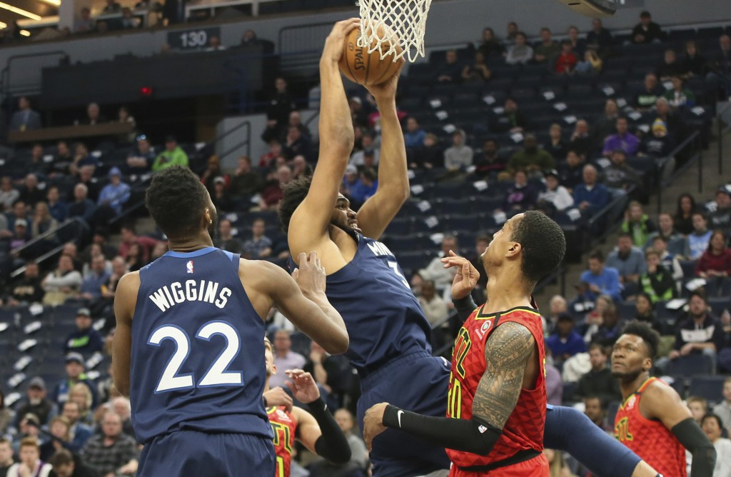 Minnesota Timberwolves' Karl-Anthony Towns, center, grabs a rebound over Atlanta Hawks' John Collins in the first half of an NBA basketball game Wedne...