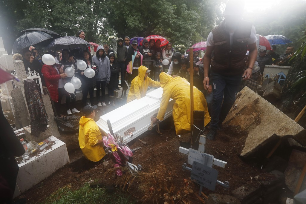 A coffin containing the remains of one of three children shot dead in a video-game arcade, is lowered into a freshly dug grave in Uruapan, Mexico, Wed...