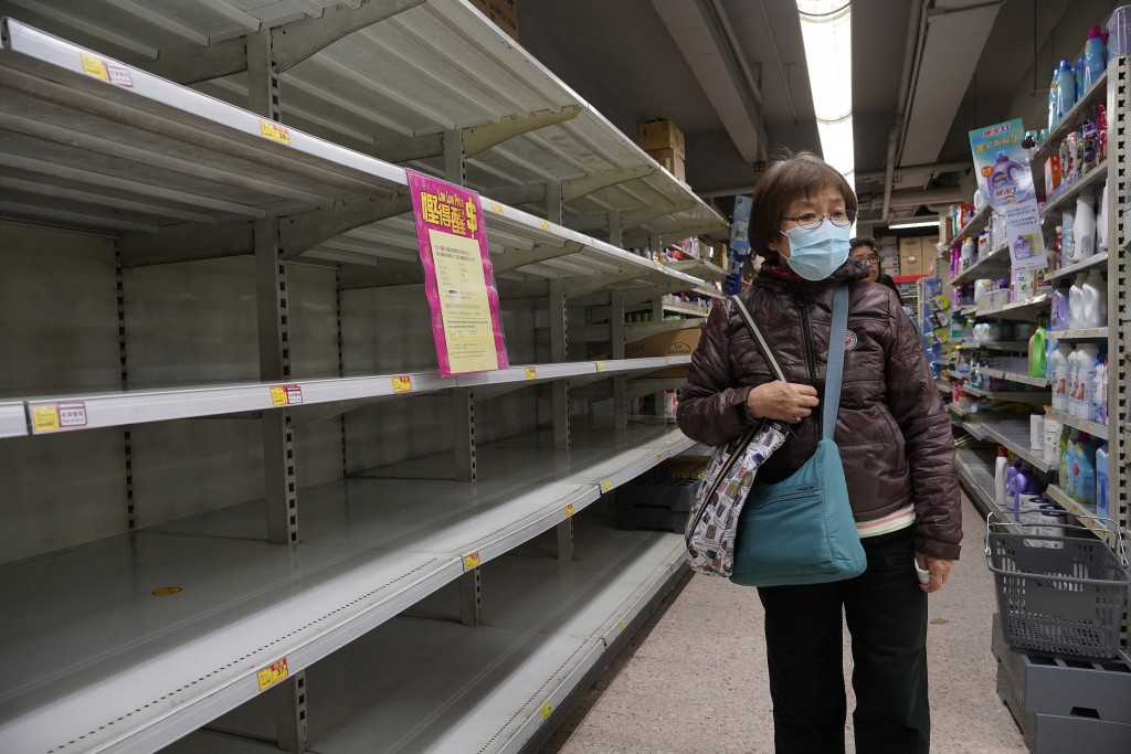 A woman wearing face mask walks past empty shelf of tissue papers at supermarket in Hong Kong, Thursday, Feb. 6, 2020. Ten more people were sickened w...
