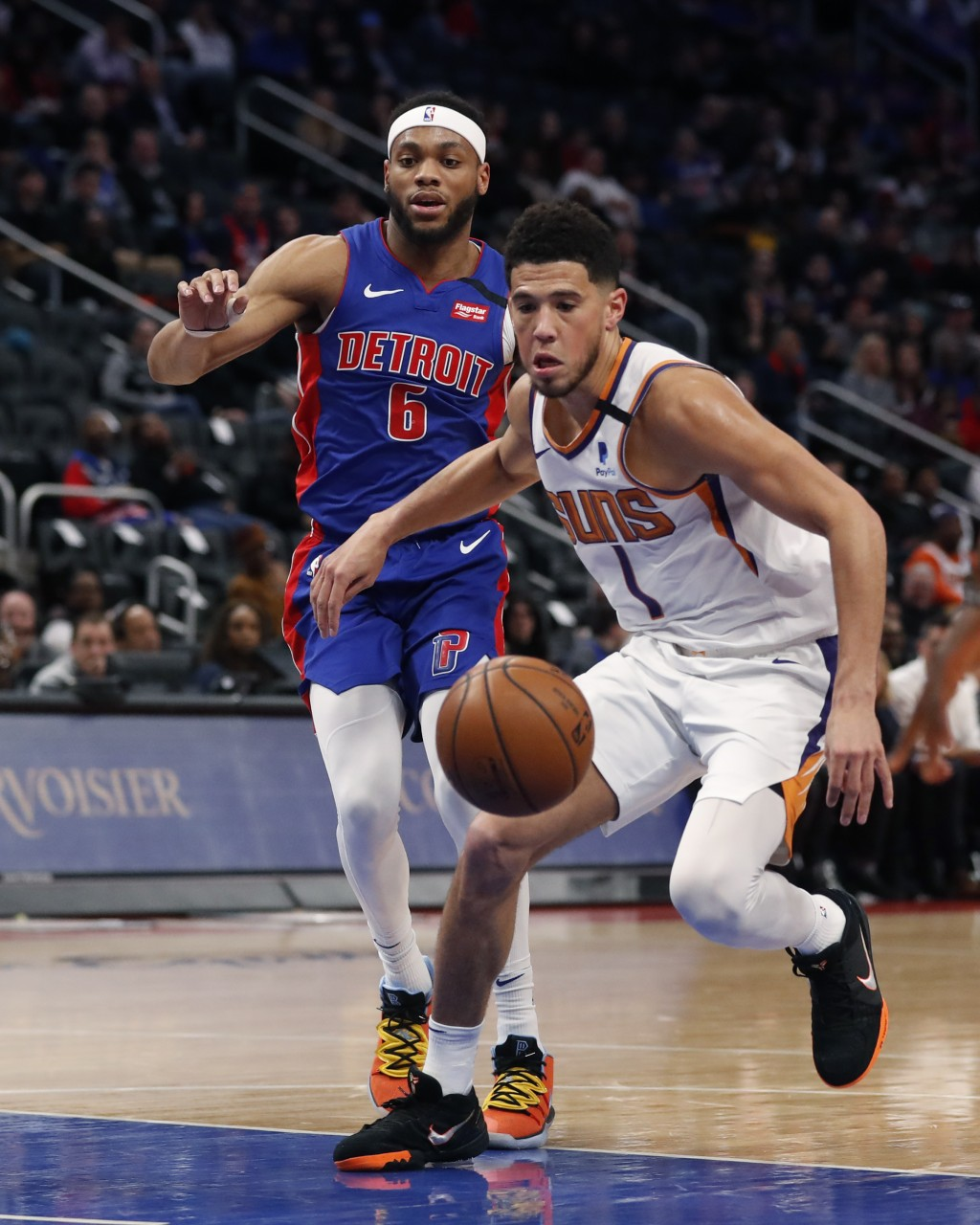 Phoenix Suns guard Devin Booker (1) chases the loose ball next to Detroit Pistons guard Bruce Brown (6) during the first half of an NBA basketball gam...