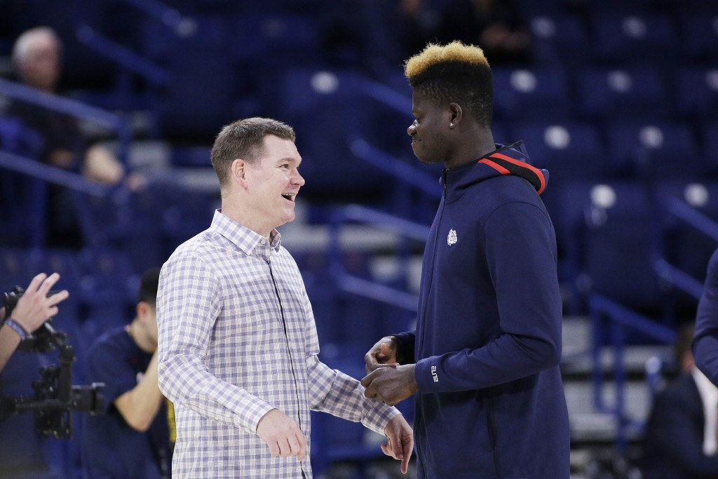 FILE - In this Nov. 5, 2019, file photo, Gonzaga assistant coach Tommy Lloyd, left, and academic redshirt Oumar Ballo, of Mali, speak before an NCAA c...