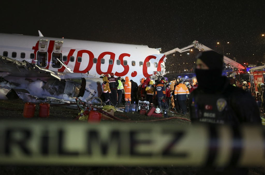 Police secure the area as rescue members and firefighters around the wreckage of a plane after it skidded off the runway at Istanbul's Sabiha Gokcen A...