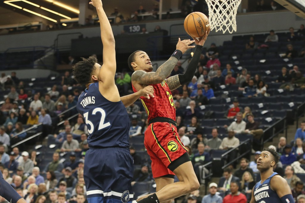 Atlanta Hawks' John Collins, right, lays up a shot in front of Minnesota Timberwolves' Karl-Anthony Towns in the second half of an NBA basketball game...