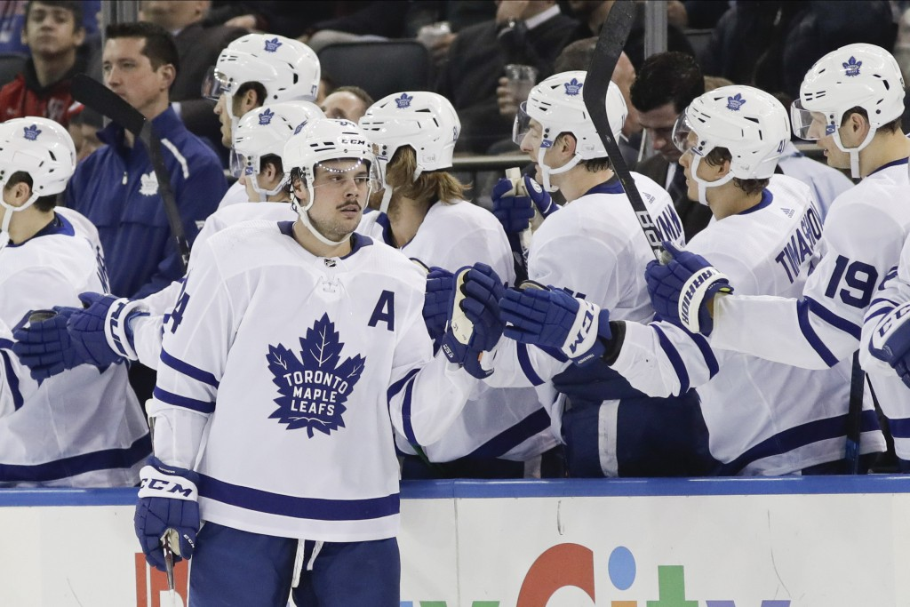 Toronto Maple Leafs' Auston Matthews (34) celebrates with teammates after scoring a goal during the second period of an NHL hockey game against the Ne...