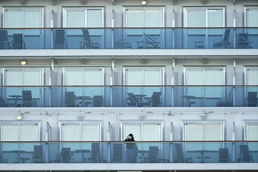 A passenger stands on the balcony of the cruise ship Diamond Princess anchored at the Yokohama Port, near Tokyo Thursday, Feb. 6, 2020. Health workers...