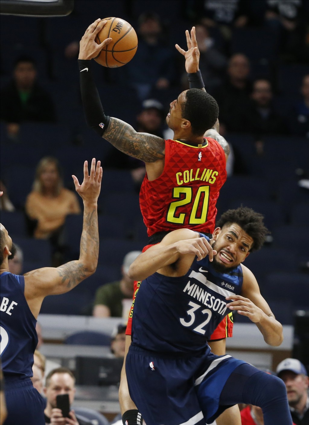Atlanta Hawks' John Collins, top, lays up a shot as Minnesota Timberwolves' Karl-Anthony Towns reacts in his attempt to block it in the first half of ...