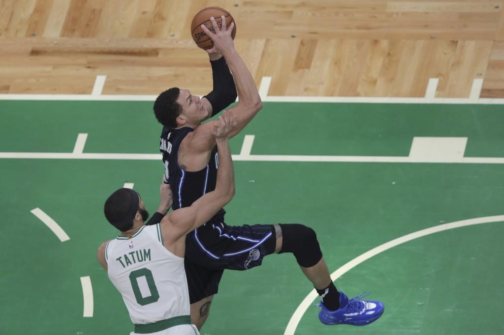 Orlando Magic forward Aaron Gordon drives to the basket past Boston Celtics forward Jayson Tatum (0) during the first quarter of an NBA basketball gam...