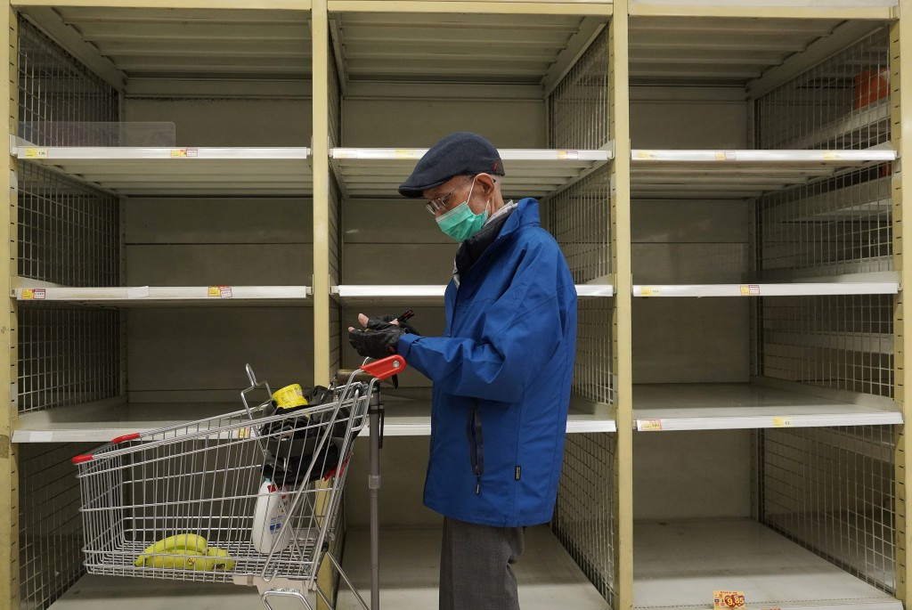 A man wearing face mask stands near an empty shelf of rice at a supermarket in Hong Kong, Thursday, Feb. 6, 2020. Ten more people were sickened with a...