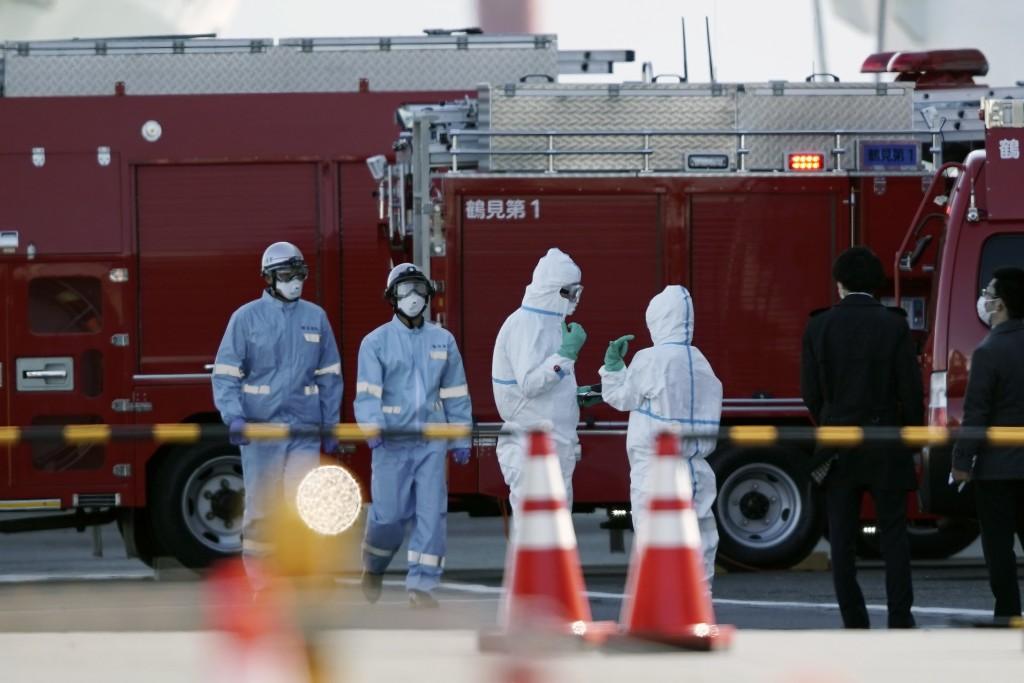 Officials wearing protective suits stand near the cruise ship Diamond Princess at Yokohama Port in Yokohama, south of Tokyo, Thursday, Feb. 6, 2020. H...