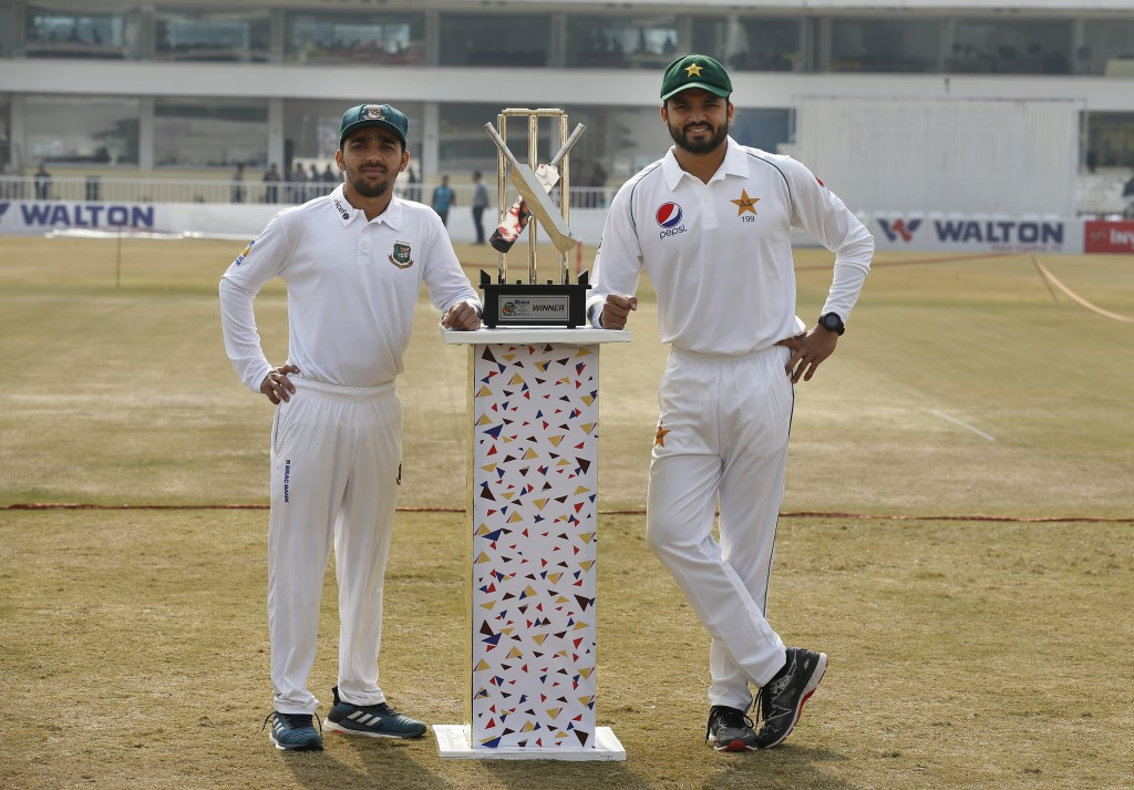 Pakistan skipper Azhar Ali, right, and his Bangladesh counterpart Mominul Haque pose for a photograph with the test series trophy at the Pindi Cricket...