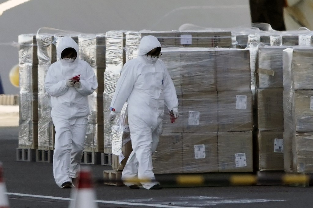 Officials in protective suits walk alongside supplies to be loaded on to the cruise ship Diamond Princess which is anchored at Yokohama Port in Yokoha...