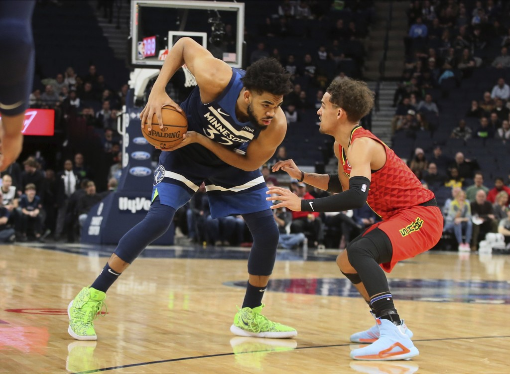 Minnesota Timberwolves' Karl-Anthony Towns, left, keeps his eyes on Atlanta Hawks' Trae Young in the first half of an NBA basketball game Wednesday, F...