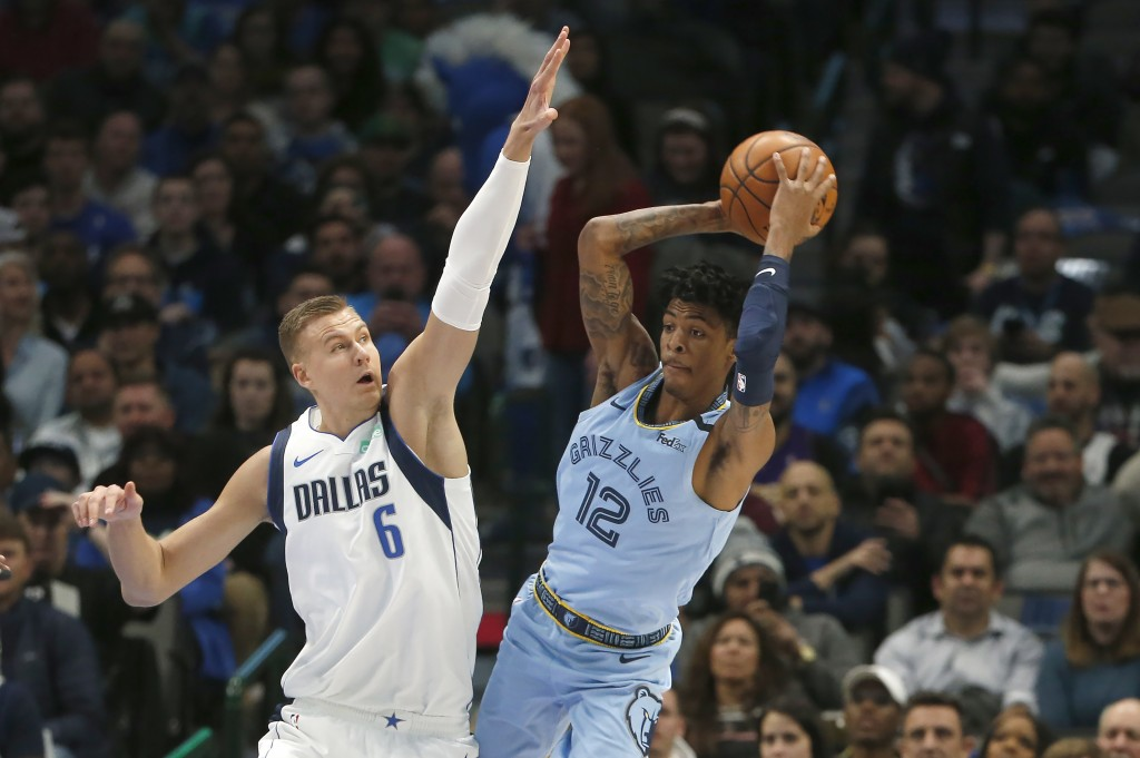 Dallas Mavericks forward Kristaps Porzingis (6) goes up to stop Memphis Grizzlies guard Ja Morant (12) from making a pass during the first half of an ...