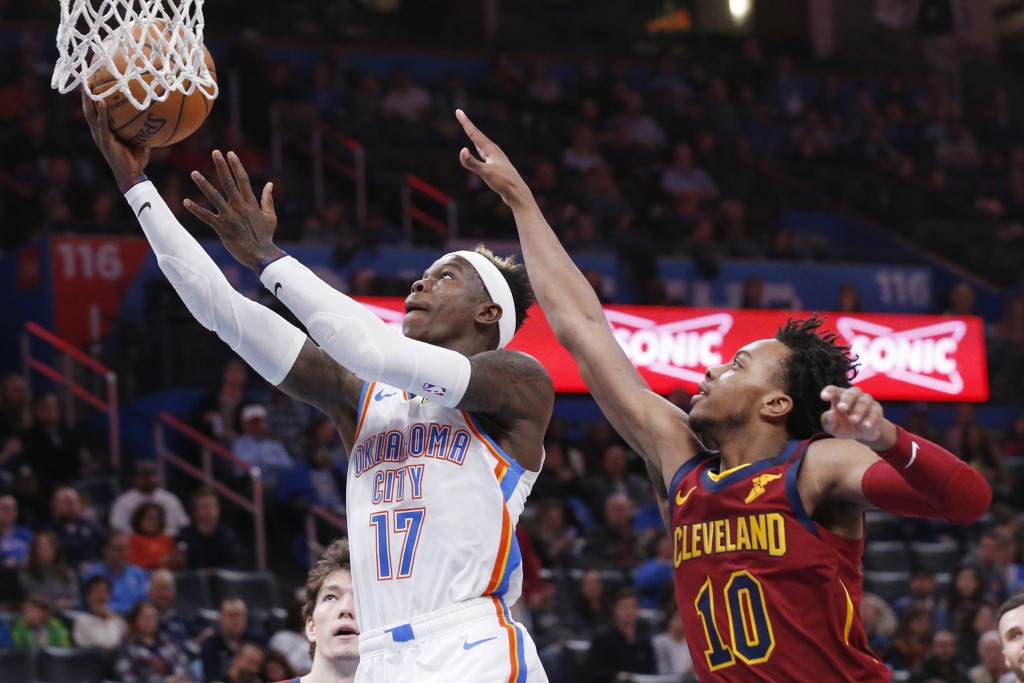 Oklahoma City Thunder guard Dennis Schroeder (17) shoots in front of Cleveland Cavaliers guard Darius Garland (10) during the first half of an NBA bas...