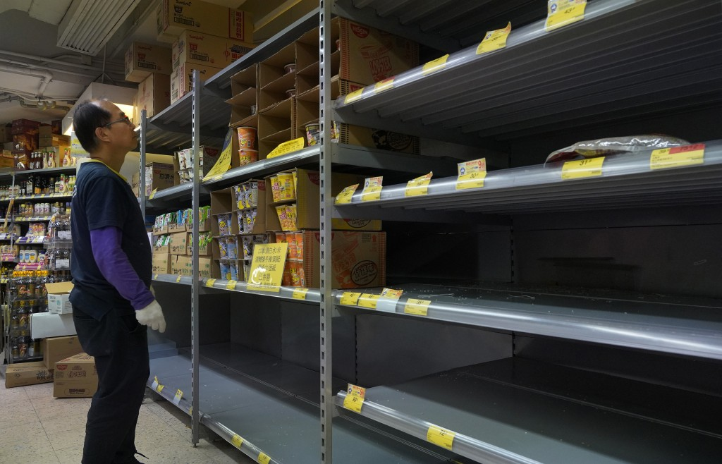 A worker checks empty shelf of rice at a supermarket in Hong Kong, Thursday, Feb. 6, 2020. Ten more people were sickened with a new virus aboard one o...