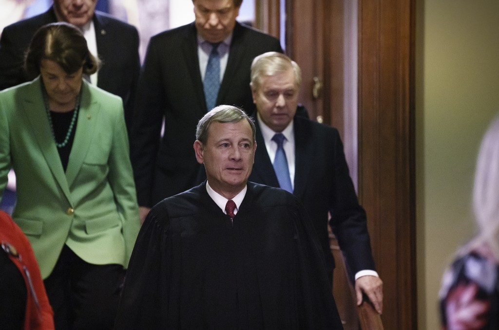 Chief Justice of the United States John Roberts, followed by Sen. Dianne Feinstein, D-Calif., left, and Senate Judiciary Committee Chairman Lindsey Gr...