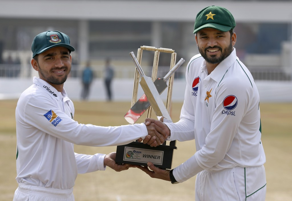 Pakistan skipper Azhar Ali, right, and his Bangladesh counterpart Mominul Haque shakes hand while they pose for a photograph with the test series trop...