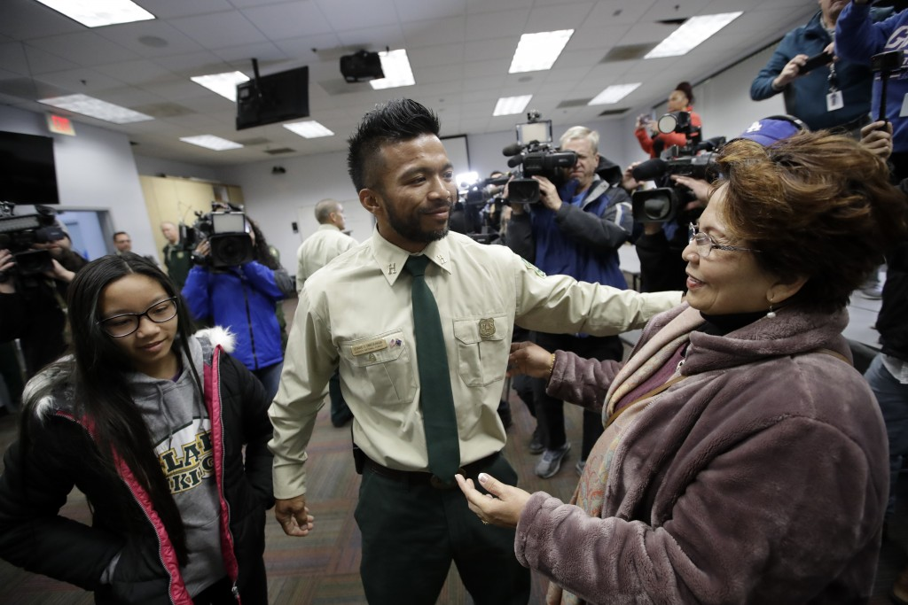 Firefighter Leonard Dimaculangan, of Pasadena, Calif. center, is greeted by his mother Lucita, right, and daughter Promise, 11, after arriving from a ...