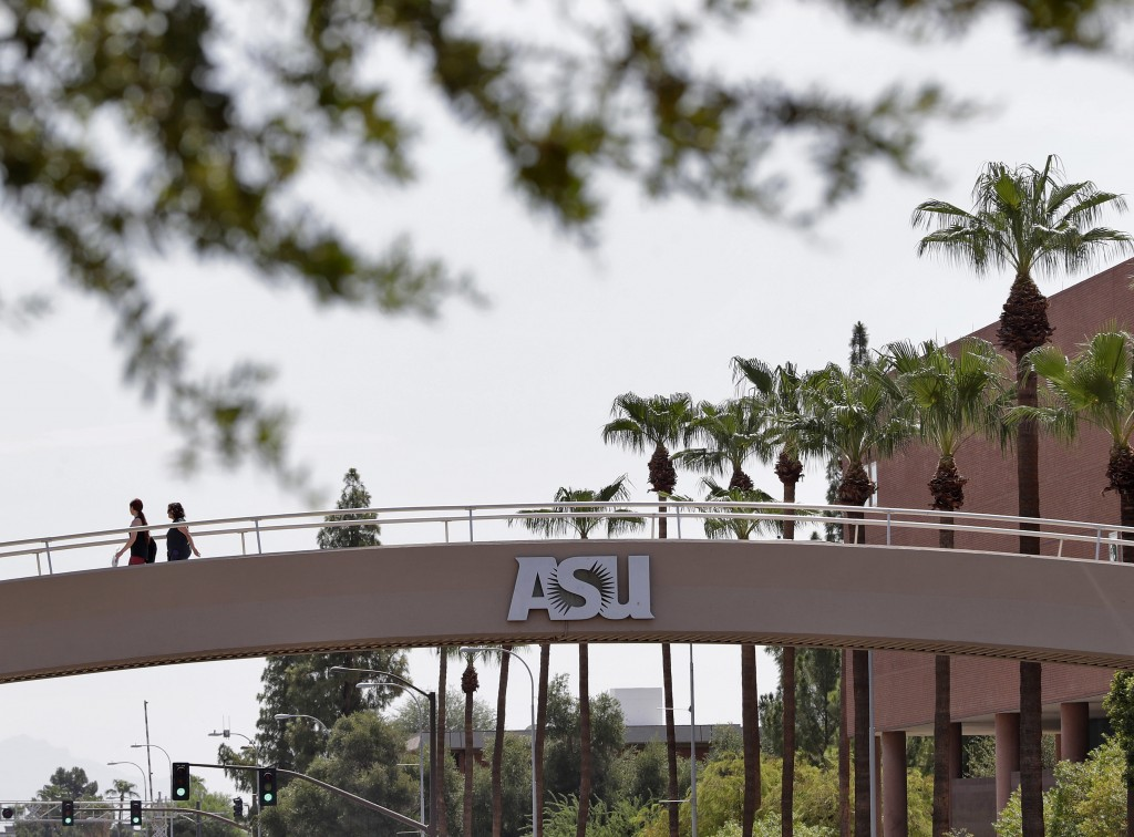 FILE - In this July 25, 2018, file photo, pedestrians cross over University Avenue on the campus of Arizona State University in Tempe, Ariz. As concer...