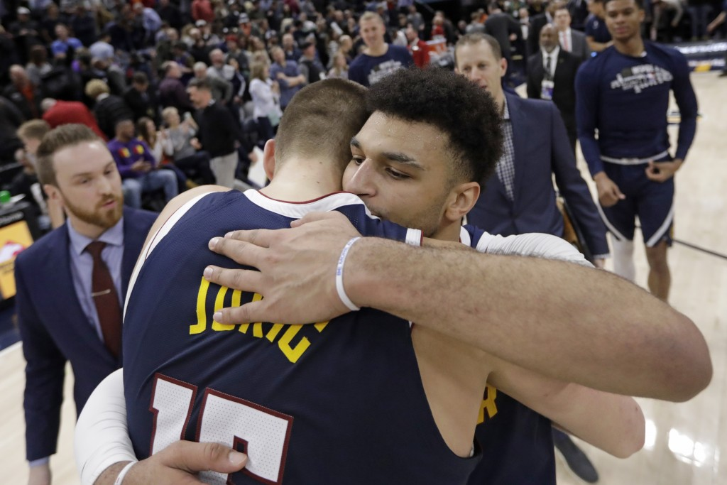 Denver Nuggets' Nikola Jokic, left, and Jamal Murray, rear, hug after the team's victory over the Utah Jazz in an NBA basketball game Wednesday, Feb. ...