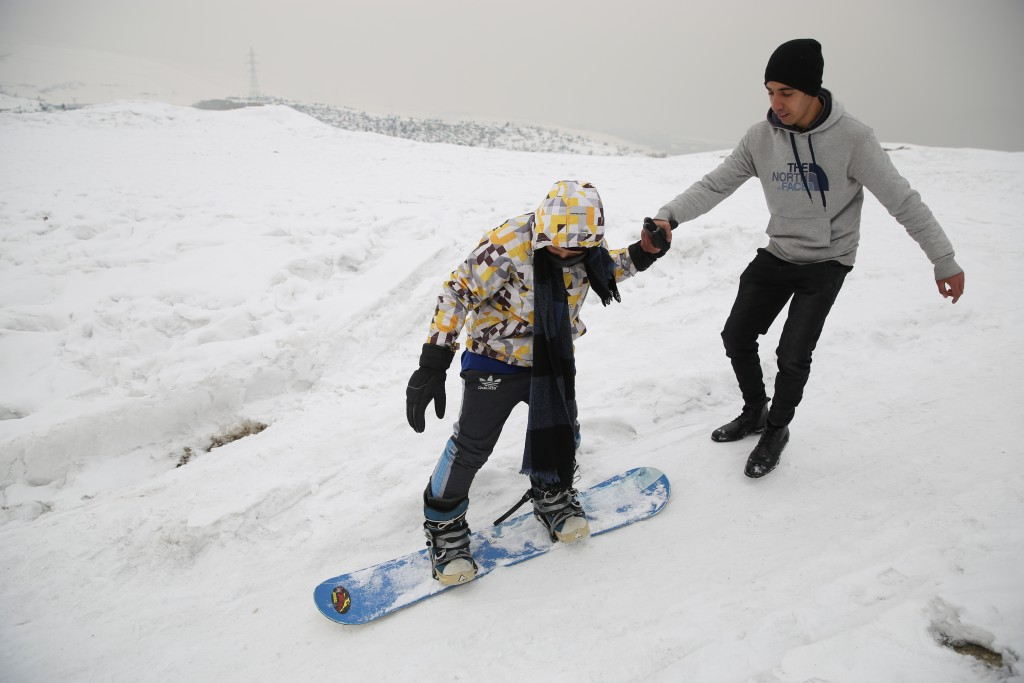 In this Friday, Jan. 24, 2020 photo, a member of the minority Hazara ethnic group, tries snowboarding with a trainer on the snow-covered hillside know...