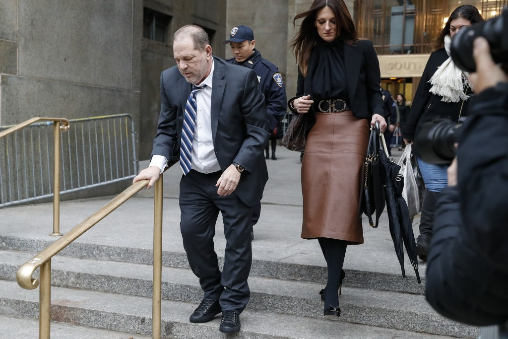 Harvey Weinstein, left, departs a Manhattan courthouse for his rape trial, Wednesday, Feb. 5, 2020, in New York. (AP Photo/John Minchillo)