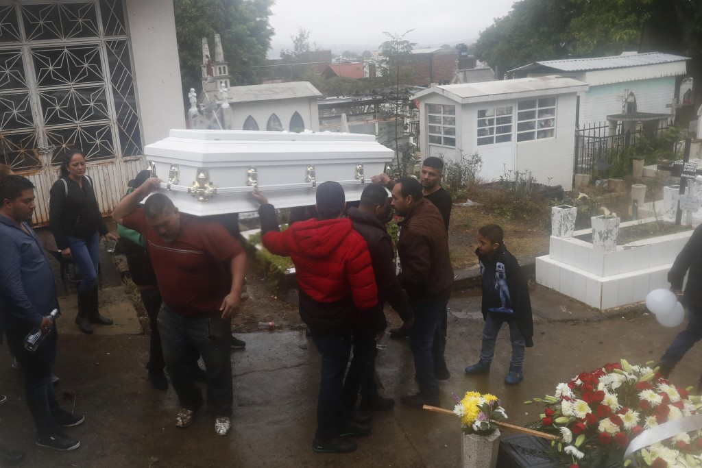 A coffin containing the remains of one of three children shot dead in a video-game arcade, is carried to a freshly dug grave in Uruapan, Mexico, Wedne...