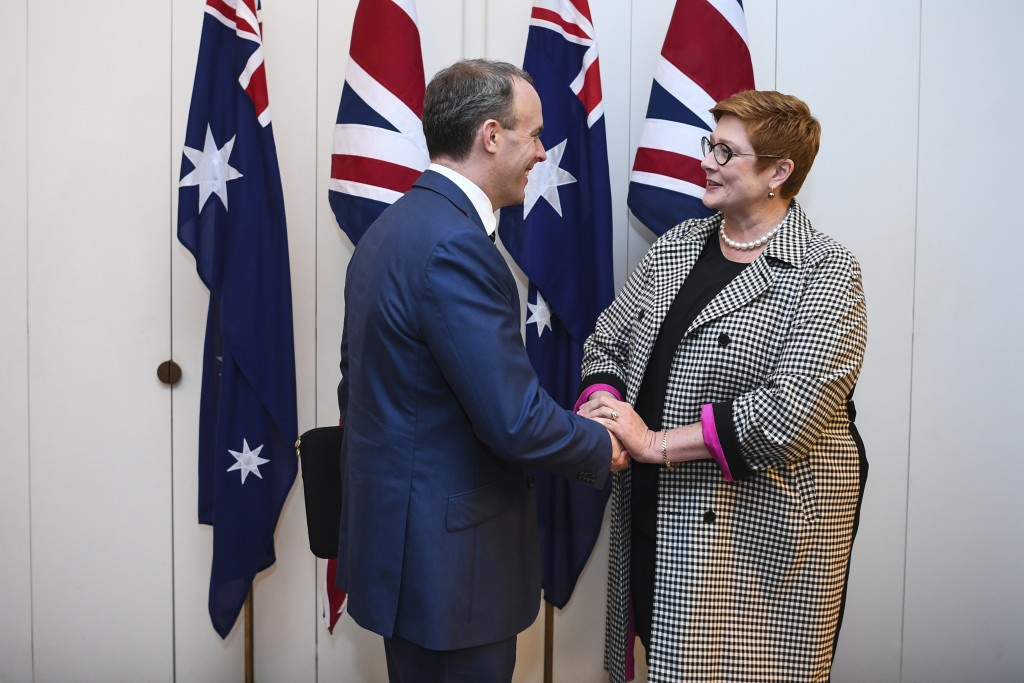 Britain's Foreign Secretary Dominic Raab, left, and Australian Foreign Minister Marise Payne shake hands ahead of a bilateral meeting at Parliament Ho...